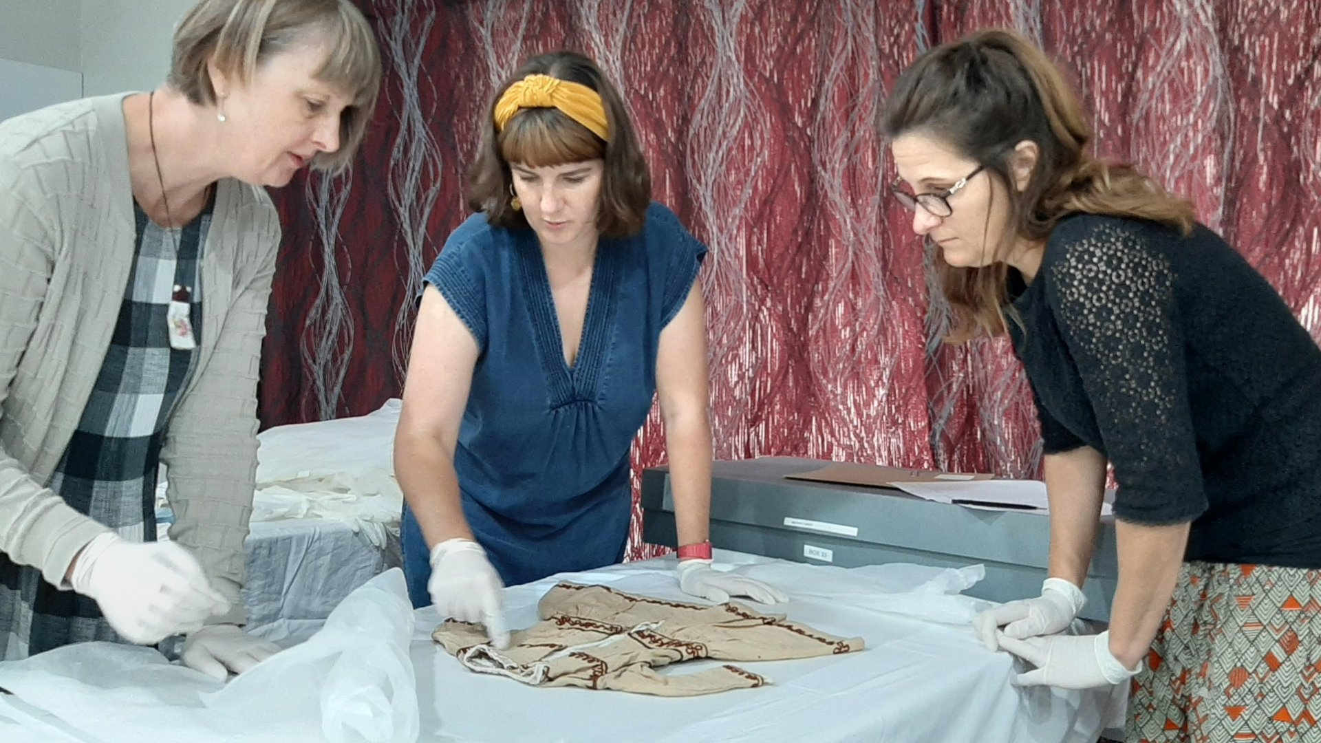Dr Stella Lange, left, inspects a Victorian-era child's dress with Jessie Bray Sharpin and Mahina Marshall before it is repacked and stored.