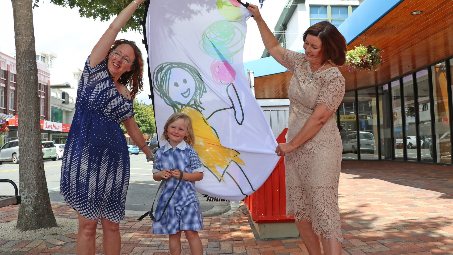 Rebekah Malthus, left, with daughter Jeanie Hicks, 5, and Mayor Rachel Reese check out the flag bearing Jeanie's artwork before it was raised outside Civic House on Tuesday.