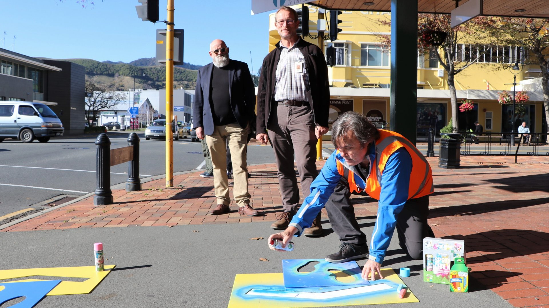 Councillor Pete Rainey (left) and Chief Medical Officer for Nelson Marlborough Health Dr Nick Baker are shown the stencils outside Civic House by City Centre Development Programme Lead Alan Gray.